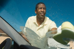 man-washing-car-windshield-scrubbing-sponge-glass