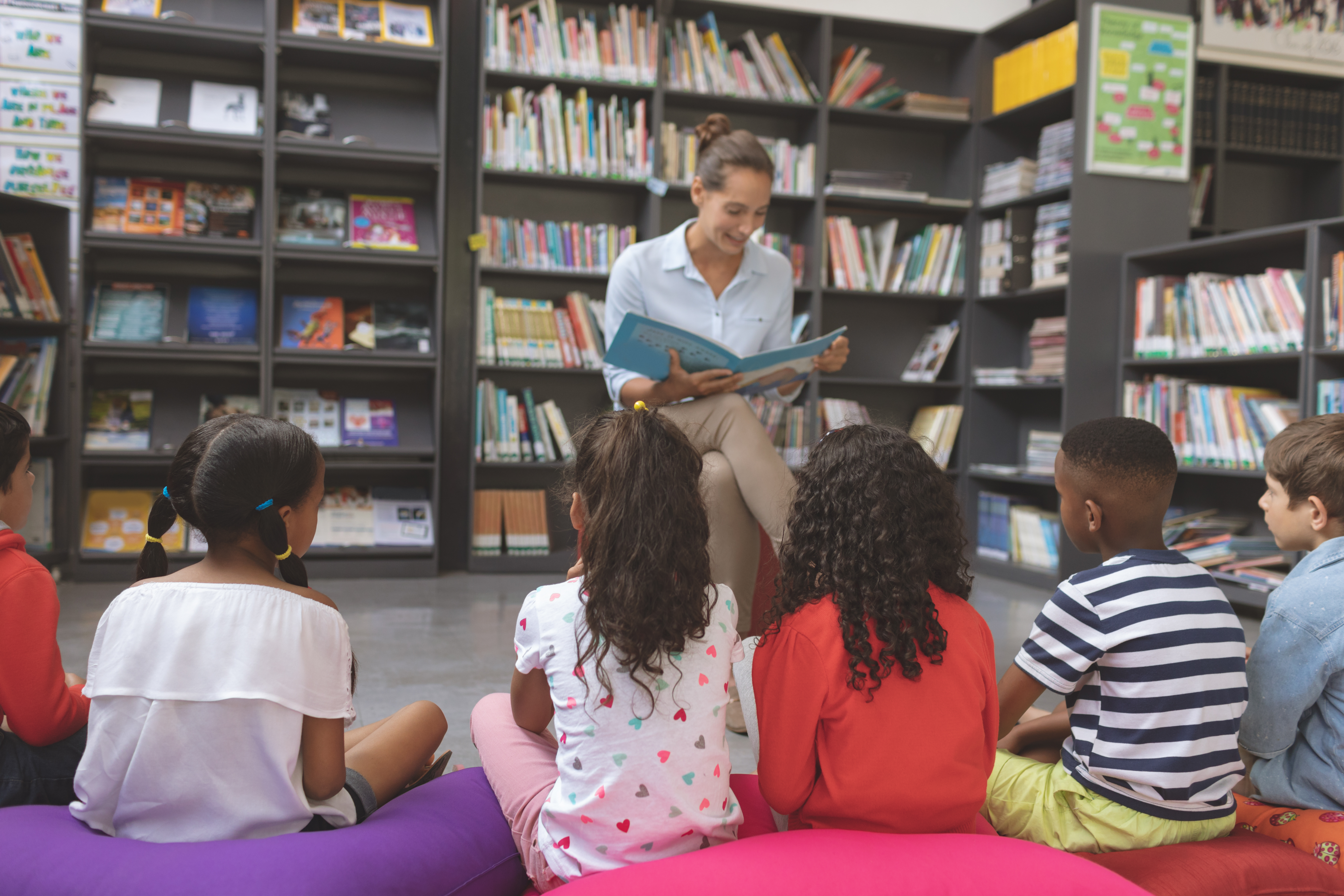 Front view of a teacher reading a story in a library to school kids sitting over big colored cushions in foreground
